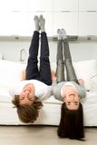 Couple upside down on sofa. Laughing royalty free stock photos