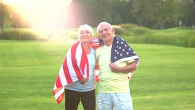 Couple with USA flag smiling. Senior people on outdoor background. Roots of strong nation. Love to sport and country stock video