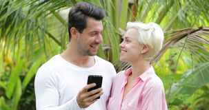 Couple Use Cell Smart Phone Embracing Talking Over Palm Trees, Young Man And Woman Chatting Online Happy Smiling. Communication Slow Motion 60 stock footage