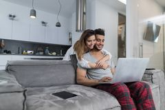 Couple Use Laptop Computer Together In Living Room, Happy Smiling Woman Embracing Man Sitting On Couch, Young People royalty free stock photography
