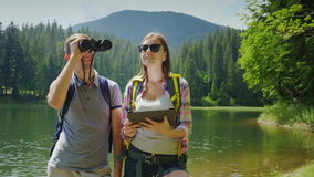 The couple uses a tablet while traveling to the lake and mountains. A man looks through binoculars, a woman on a map on. Man and woman travelers. Together they stock video