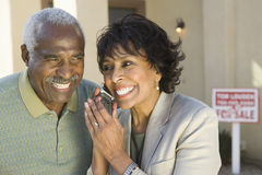 Couple Using Cell Phone In Front Of New House stock images