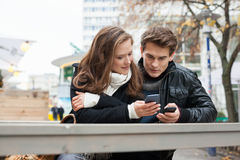 Couple Using Cell Phone While Leaning On Bench Royalty Free Stock Photo