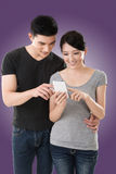 Couple using cellphone. Asian young couple using cellphone, closeup portrait royalty free stock photos