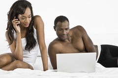 Couple Using Cellphone And Laptop In Bedroom Royalty Free Stock Photography