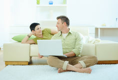 Couple using computer at home Royalty Free Stock Image
