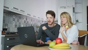 Couple using computer at kitchen counter stock video footage