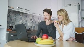 Couple using computer at kitchen counter stock footage