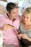 Couple using credit card and shopping with smartphone. Upper view of couple paying with credit card on mobile phone Royalty Free Stock Photography