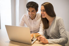 Couple using credit card to shop on line. Laptop. Indoor desk stock images
