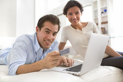 Couple using credit card to shop online at home stock photography