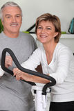 Couple using a cross trainer Royalty Free Stock Image
