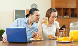 Couple using devices during breakfast Royalty Free Stock Images