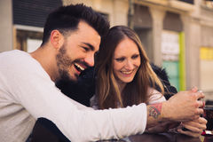 Couple using digital phone iphone and laughing in a terrace. Couple watching digital touchscreen phone iphone and laughing in a cafe terrace Royalty Free Stock Photography