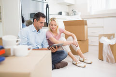 Couple using digital tablet amid boxes in house. Couple using digital tablet amid boxes in a new house Royalty Free Stock Photos