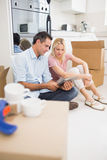 Couple using digital tablet amid boxes in house Royalty Free Stock Images