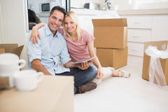 Couple using digital tablet amid boxes in new house Stock Photography