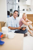 Couple using digital tablet amid boxes in a new house Royalty Free Stock Photos