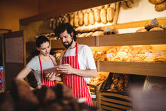 Couple using digital tablet. In bakery shop Royalty Free Stock Images