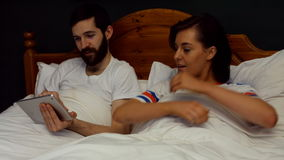 Couple using digital tablet on bed in bedroom stock footage