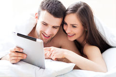 Couple using digital tablet in bed royalty free stock photography