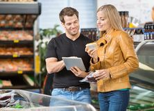 Couple Using Digital Tablet At Butcher's Shop Stock Photo