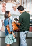 Couple Using Digital Tablet At Butcher Shop Stock Photo