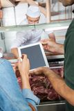 Couple Using Digital Tablet At Butchery Royalty Free Stock Photography