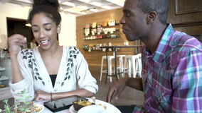 Couple Using Digital Tablet In Café Restaurant. Couple sitting at table in café using digital tablet.Shot on Sony FS700 in PAL format at a frame rate of 25fps stock footage
