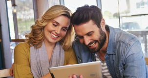 Couple using digital tablet in café. Smiling couple using digital tablet in café 4k stock video