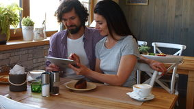 Couple using digital tablet in cafe. Affectionate couple using digital tablet in bakery shop 4k stock footage