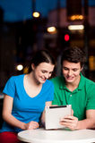 Couple using digital tablet in cafe Stock Images
