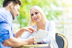 Couple using digital tablet at cafe Royalty Free Stock Photos