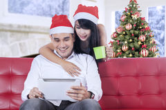 Couple using digital tablet in christmas day Royalty Free Stock Photography