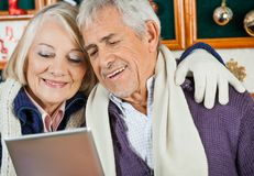 Couple Using Digital Tablet At Christmas Store Stock Photography