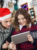 Couple Using Digital Tablet At Christmas Store Stock Images