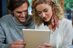 Couple using digital tablet in coffee shop Stock Photo