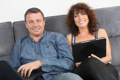 Couple using a digital tablet on couch at home Stock Photo