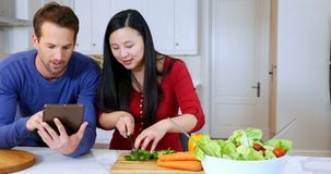 Couple using digital tablet while cutting vegetable in kitchen 4k. Couple using digital tablet while cutting vegetable in kitchen at home 4k stock video footage
