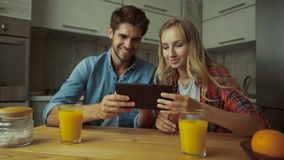 Couple using a digital tablet while having breakfast at home. stock footage