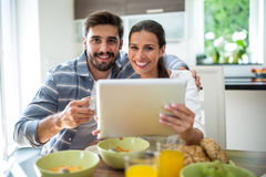 Couple using digital tablet while having breakfast at home Stock Photo