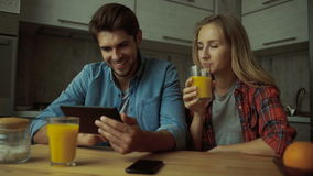 Couple using a digital tablet while having breakfast at home. Young couple using tablet and phone in the kitchen stock video