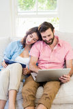 Couple using digital tablet and laptop Royalty Free Stock Images