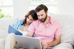 Couple using digital tablet and laptop in living room Stock Photos