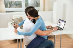 Couple using digital tablet and laptop Stock Image