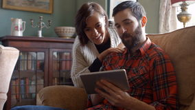 Couple using digital tablet in living room stock video