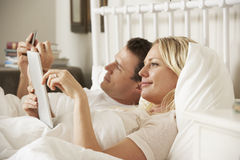 Couple Using Digital Tablet And Mobile Phone In Bed At Home Royalty Free Stock Images