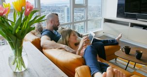 Couple using digital tablet and mobile phone in living room 4k. Couple using digital tablet and mobile phone in living room at home 4k stock video