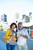 Couple using digital tablet and mobile phone on walkway Royalty Free Stock Photos
