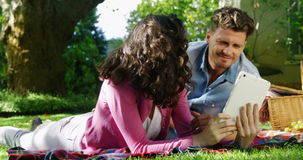 Couple using digital tablet in park stock video